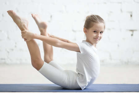 Smiling girl child practicing yoga, stretching in dhanurasana exercise, bow pose, working out wearing sportswear, t-shirt, pants, indoor full length, white loft studio background